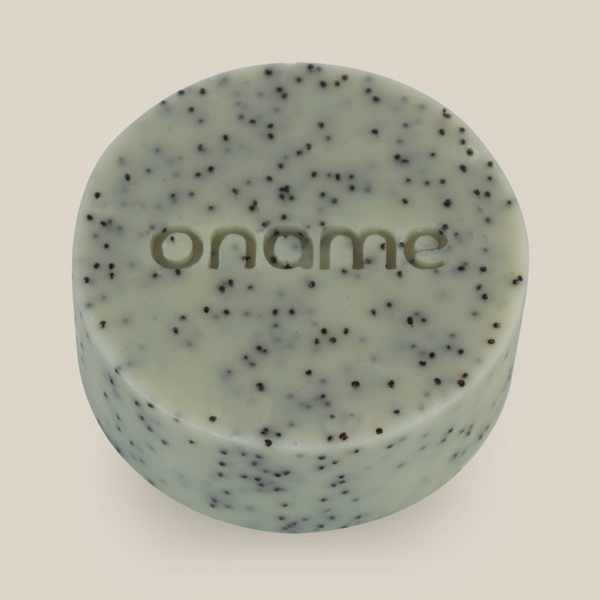 Oname Rosemary & Poppy Seed soap side view on a brown background