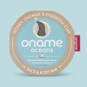 Oname Honey, Oatmilk & Rhassoul Clay soap on a blue background
